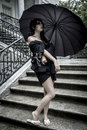 Japanese look pretty young woman with black umbrella under aut autumn rain in a palace Royalty Free Stock Photography