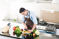 Japanese man preparing salad and cooking in kitchen Royalty Free Stock Photo