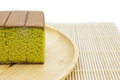 Japanese Matcha green tea cake cheesecake on wooden plate and traditional mat  white background. Royalty Free Stock Photo