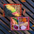Japanese meal bento in paper boxes on a wood bench Royalty Free Stock Images