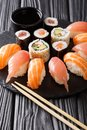 Japanese menu. Tasty set of sushi with salmon and tuna, California rolls, maki, soy sauce closeup. vertical Royalty Free Stock Photo