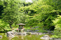 Japanese outdoor stone lantern, green plants in zen garden Royalty Free Stock Photo