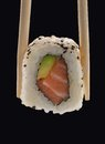 Japanese roll sushi on chopsticks on black background Royalty Free Stock Photos
