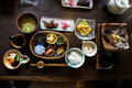 Japanese ryokan breakfast dishes including cooked white rice, grilled fish, fried egg, soup, mentaiko, pickle, seaweed, hot plate