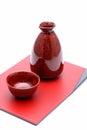 Japanese sake bottle and cups on tray isolated on white background Royalty Free Stock Photo