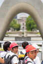 Japanese school kids at memorial cenotaph hiroshima peace memorial park japan july a group of children visits the in the center of Stock Photos