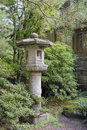 Japanese stone lantern in garden landscape with trees plants and shrubs during fall season Stock Photos