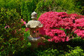 Japanese stone lantern in a garden red azalia bushes surrounding Stock Photos
