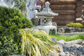 Japanese stone lantern garden torch stands on grass on the background is a wooden house and a statue in the foreground is a bush Royalty Free Stock Photography