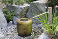 Japanese style pump fountain water running from a bamboo tube into a stone vase Royalty Free Stock Photos