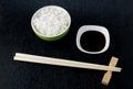 Japanese sushi chopsticks over soy sauce bowl, rice on black bac Royalty Free Stock Photo