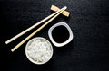 Japanese sushi chopsticks over soy sauce bowl, rice on black Royalty Free Stock Photo