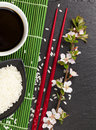 Japanese sushi chopsticks, soy sauce bowl, rice and sakura bloss Royalty Free Stock Photo