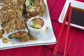 Japanese sushi and soy sauce in white plates with red chopsticks Royalty Free Stock Photo