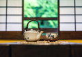 Japanese tea ceremony teapot and bowl on a table in a traditional room in front of shoji screen windows Stock Photos