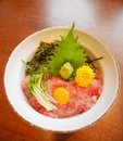 Japanese traditional cuisine minced raw tuna belly on rice bowl maguro don with egg yolk, bean sprouts, wasabi Royalty Free Stock Photo