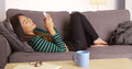 Japanese woman happily texting and laughing on couch Stock Photo