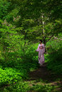 Japanese young woman in spring forest beautiful wearing pink kimono walking along the path and touching branch of shrub blooming Stock Images
