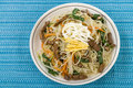Japchae stir fried korean sweet potato noodles with vegetables mushrooms and beef garnished with slices of fried egg and sesame Stock Photography