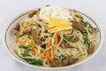 Japchae stir fried korean sweet potato noodles with vegetables mushrooms and beef garnished with slices of fried egg and sesame Stock Photo