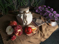 Jar,apples,pomegranate,coffe cup with books and orange on canvas drapery conceptual still-life Royalty Free Stock Photo