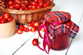 Jar with cherries on the white wooden table closeup Royalty Free Stock Photo