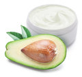 Jar of cream and slices of avocado on a white background Royalty Free Stock Photography