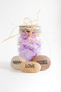 Jar of flower petals with happy love and kisses rocks a mason filled purple tied a raffia bow at the base are three one the word Stock Photo