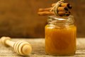 Jar of honey with drizzler and cinnamon on wooden background Royalty Free Stock Photo