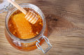 Jar of honey with honeycomb and dipper on wooden background Royalty Free Stock Photo