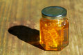 Jar of honey with honeycomb on wood a pure amber colored local glistens in the sun inside the is also a piece the it came from Royalty Free Stock Images