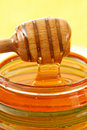Jar of honey with wood stick Stock Photos