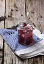 Jar of jam plum and juniper on old wooden table Stock Photography