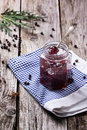Jar of jam plum and juniper on old wooden table Royalty Free Stock Photography