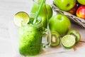 Jar mug with fresh green vegetable smoothie, bottle with fruit juice, apples in basket, lime, kiwi,bright sun fleck Royalty Free Stock Photo