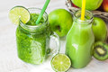 Jar mug with green vegetable smoothie and fruit juice in bottle with straw, apples, lime, kiwi,outdoors Royalty Free Stock Photo