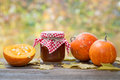 Jar of pumpkin jam puree or sauce and small ripe pumpkins on wooden table autumn still life selective focus Royalty Free Stock Photography