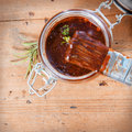 Jar of savory spicy basting sauce overhead view an open with a brush and sprig fresh rosemary on a wooden table with Royalty Free Stock Photo