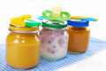 Jars with baby food spoons and dummy isolated on white Stock Photography