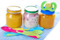 Jars with baby food spoons and dummy isolated on white Royalty Free Stock Photos