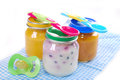 Jars with baby food spoons and dummy isolated on white Royalty Free Stock Photography
