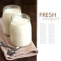 Jars of fresh natural yogurt with spoons on wooden background Royalty Free Stock Photos