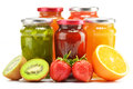 Jars of fruity jams on white preserved fruits composition with Royalty Free Stock Photos
