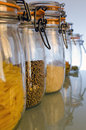 Jars in the kitchen cupboard containing filled with pasta lentils and rice primary focus is on lentils Royalty Free Stock Photos