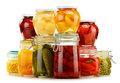 Jars with pickled vegetables and fruity compotes on white background preserved food Stock Photos