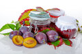 Jars of plum jams homemade in with fresh plums and autumn leafs on background Royalty Free Stock Image