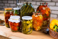 Jars of Preserved Vegetables on Wooden Table Royalty Free Stock Photo