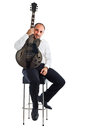 Jazz is my life a well dressed musician sitting on a stool and holding a guitar Stock Photo