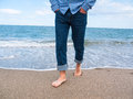 Jeans on a beach man in walking along the coast Royalty Free Stock Photos