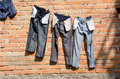 Jeans on clothesline drying clothes line against red brick wall Stock Photo